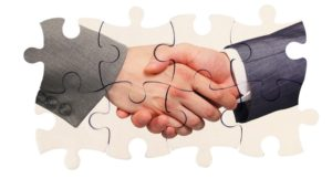 shaking hands inside puzzle pieces